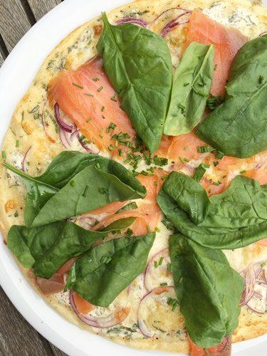 Pizza à la crème, oignons rouges, saumon fumé et pousses d'épinard